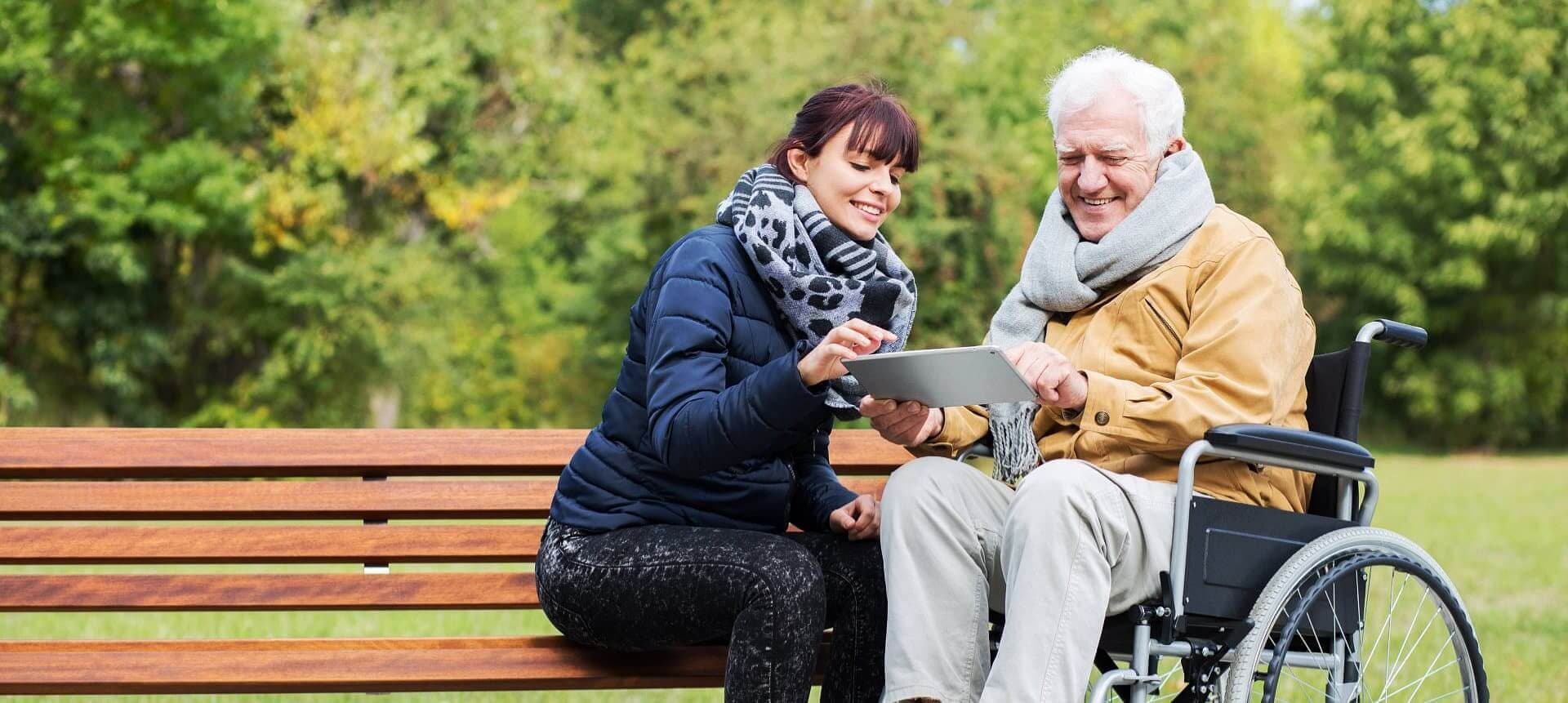 adult woman assisting senior man using a tablet